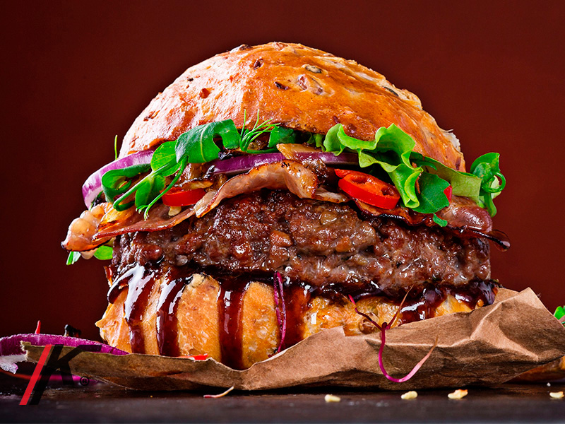 Angus premium burger served in a bun with tomato, sauce